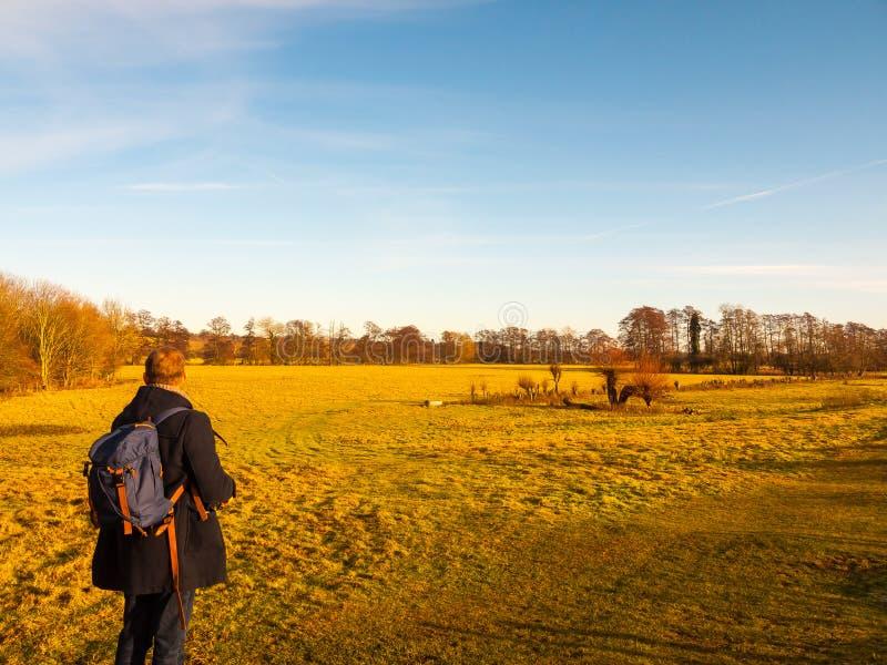 Se promener par la personne de champ de campagne par derrière le ciel bleu photographie stock
