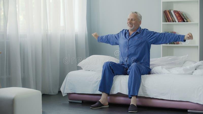 Se réveillant complètement du retraité gai d'énergie faisant la gymnastique de matin, nouveau jour photo libre de droits