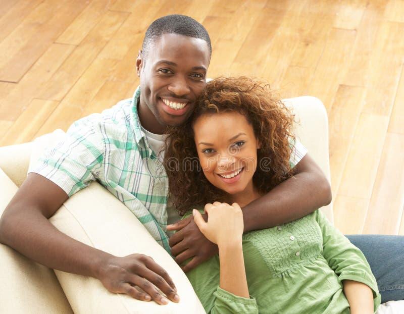 Se reposer de détente de jeunes couples romantiques sur le sofa images stock