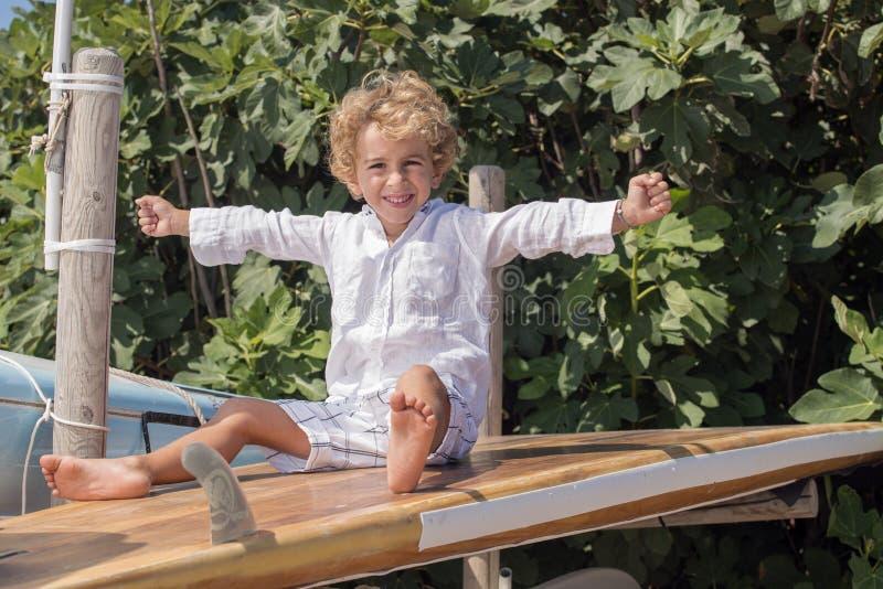 Se reposer de sourire de jeune garçon sur des planches de surf images stock