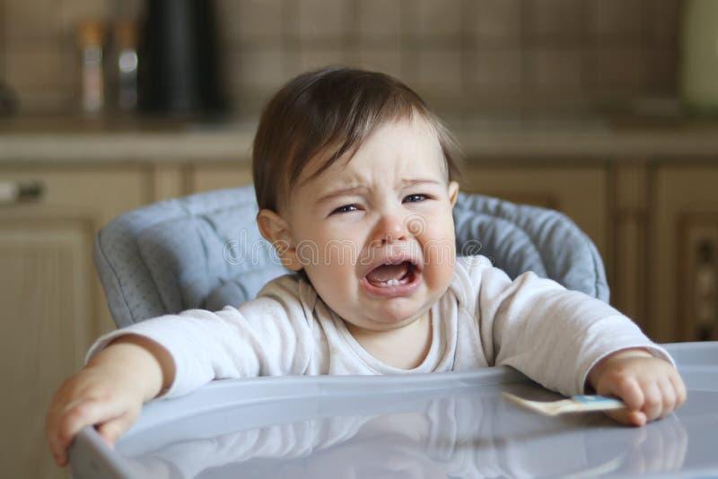 Se reposer pleurant de petit bébé affamé dans la chaise d'alimentation élevée avec la cuillère dans sa main, image stock