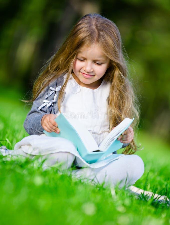 Se reposer sur la fille d'herbe lit le livre photos stock