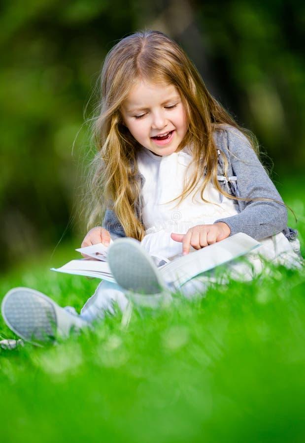 Se reposer sur la fille d'herbe verte lit le livre photo libre de droits