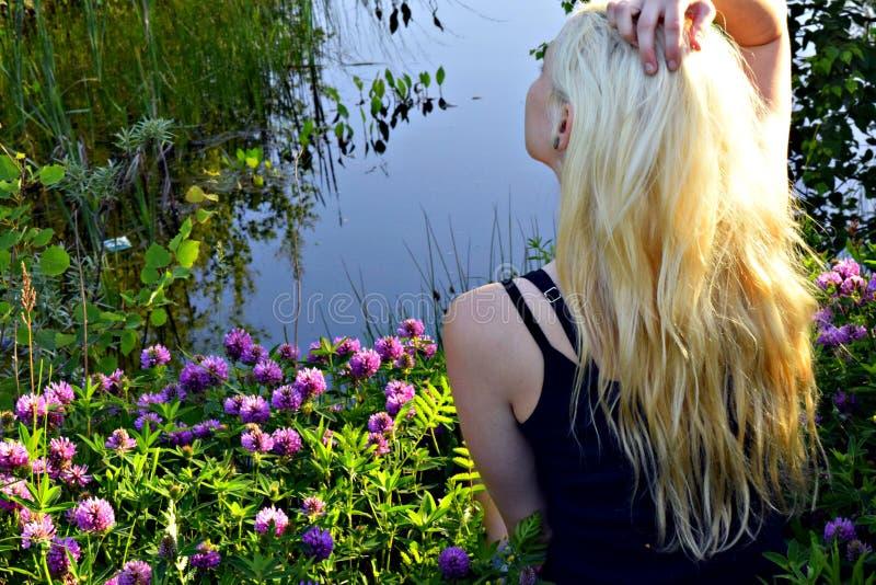 Se reposer sur un tapis floral de trèfle près de la forêt d'une fille blonde de petit lac photos stock