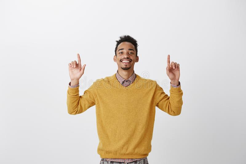 Se sentir comme le gagnant Portrait de type heureux satisfaisant d'afro-américain dans le pull jaune, soulevant des index et photographie stock libre de droits