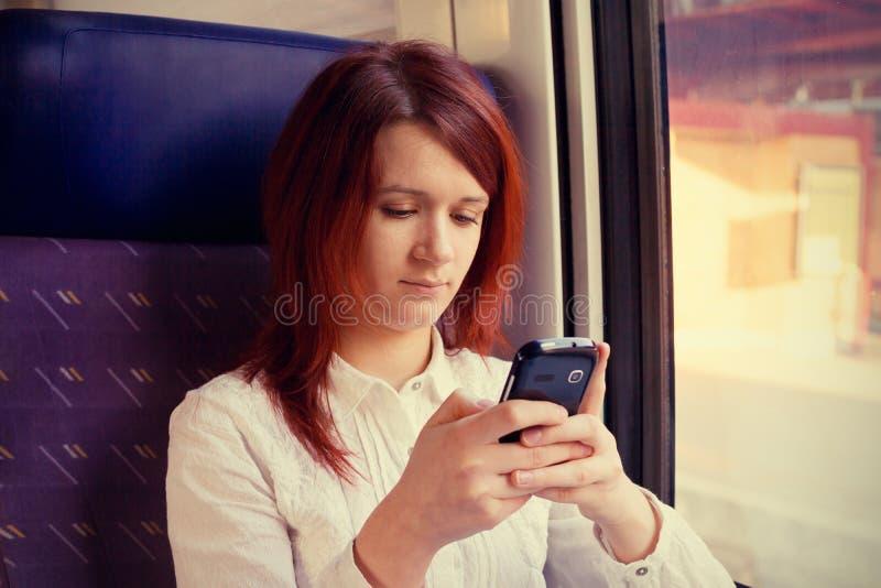 Se sentir de sourire de jeune femme décontracté et parler au téléphone portable voyageant près de la fenêtre de train images stock