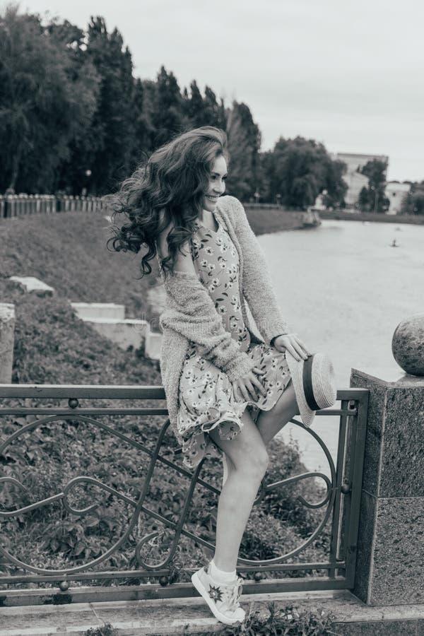 se sienta en una cerca, en las manos de un sombrero, de un vestido en una flor y de un suéter Muchacha hermosa imagen contra la p imagen de archivo libre de regalías