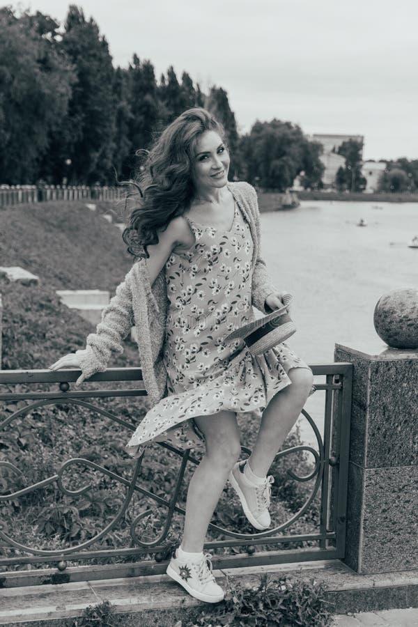 se sienta en una cerca, en las manos de un sombrero, de un vestido en una flor y de un suéter Muchacha hermosa imagen contra la p imagen de archivo