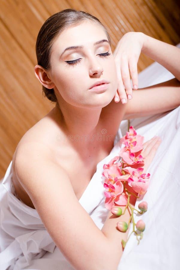 se situer de détente de jolie femme sexy de brune jeune dans le salon de station thermale tenant la fleur d'orchidée observe l'im photos stock
