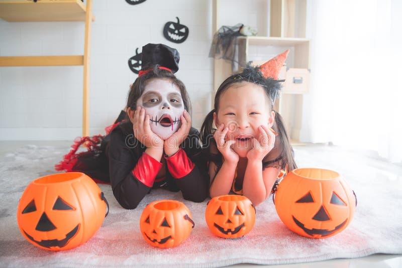 Se situer et sourire de filles dans la chambre décorée pour le jour de Halloween photographie stock
