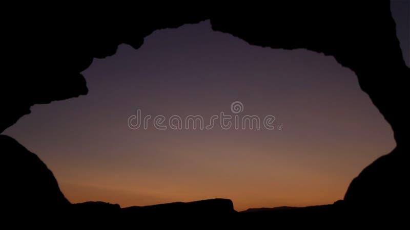 Se solnedgång till och med helhet i havsvägg på skymning skjutit Att se solnedgången till och med hålet i vaggar royaltyfri foto