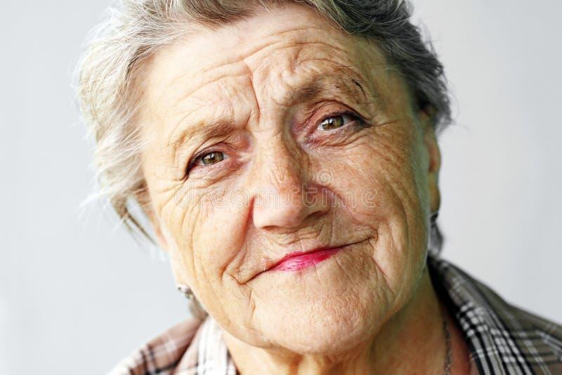 Se ståenden för gammal kvinna på en grå bakgrund royaltyfri bild