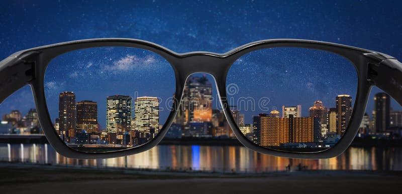 Se staden på natten med stjärnklar himmel till och med exponeringsglas arkivbilder