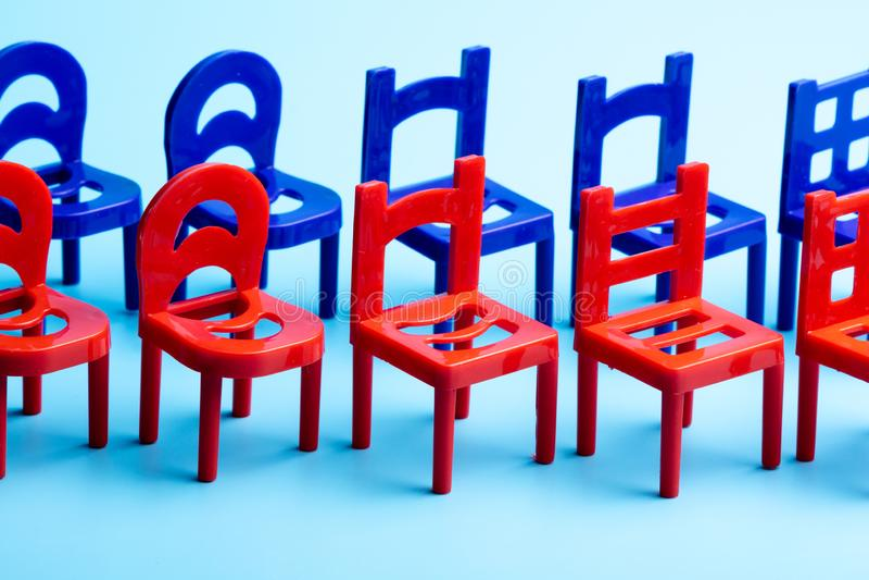 Se tenant dans deux rangées des chaises rouges et bleues, plan rapproché des chaises en plastique avec les dos découpés image libre de droits