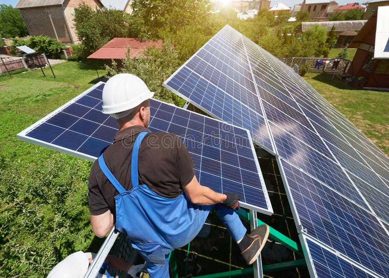 Se tenant sur la haute échelle métallique, travailleur gardant le panneau solaire image stock