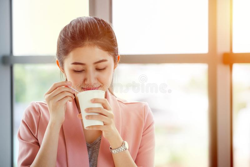 se tenir de femme d'affaires et tasse de café de papier potable détendant dessus images stock