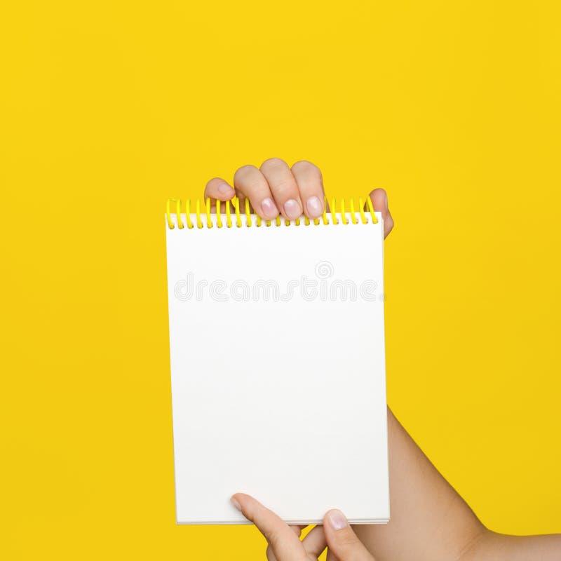 Se tenir femelle de mains ouvrent un bloc-notes vide pour des notes sur le fond jaune image stock