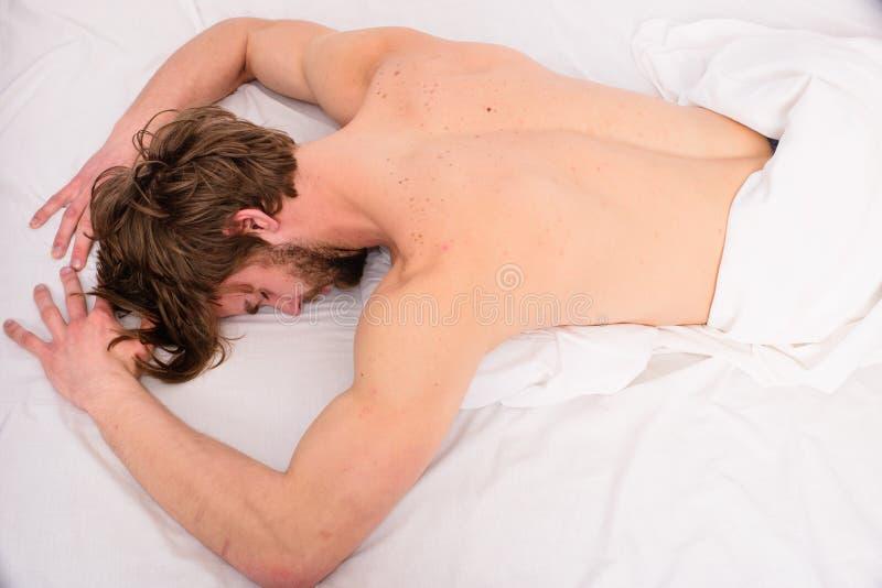 Se till den understöd madrassen som är bekväm och Man den bästa sikten för trött utmattad säng för grabben naken tillbaka avslapp royaltyfri fotografi