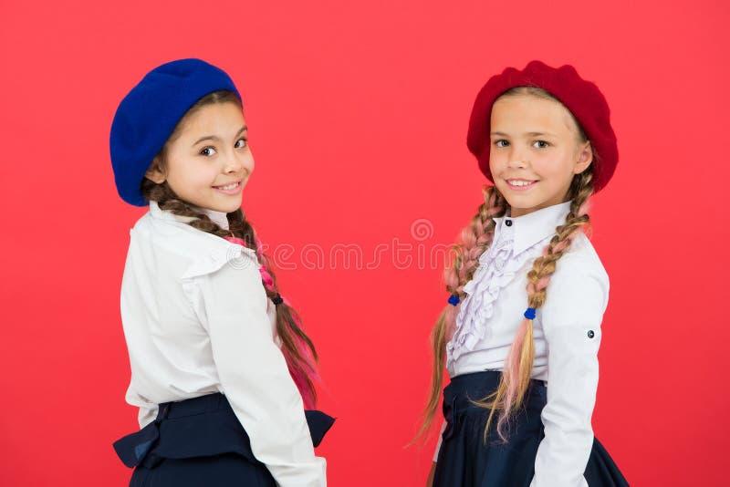 Se tillbaka tillbaka skola till Utbildning utomlands ungemode små flickor i fransk basker Internationell utbytesskola royaltyfri foto