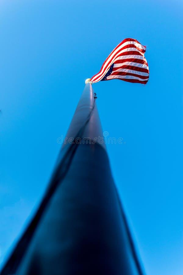 Se upp längs en flaggstång, in mot amerikanska flaggan, stjärnorna & banden som vinkar i vinden, mot en härlig blå himmel på a royaltyfri bild