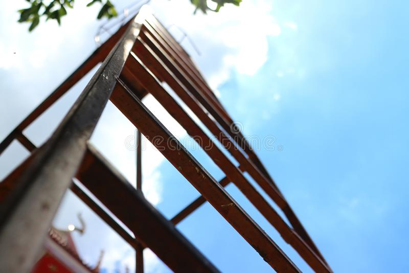 Se upp på ståltrappan, himmelbakgrunden, molnen och solljuset royaltyfria foton