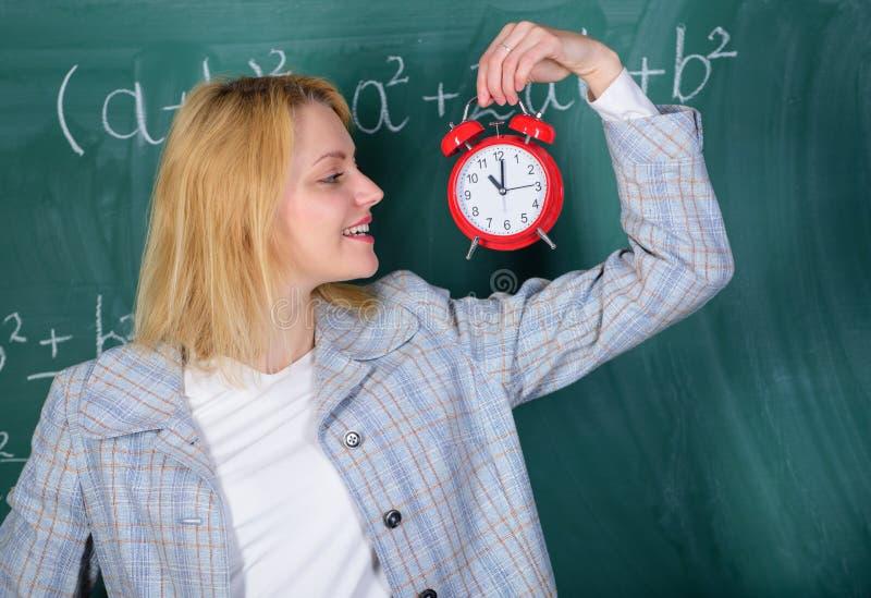 Se utbildare för arbetskraft för hängivet lärarekomplement kvalificerade Alltid i rätt tid Ringklocka för kvinnalärarehåll henne arkivbild