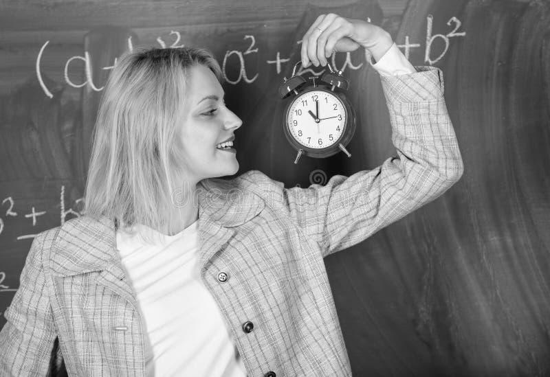 Se utbildare för arbetskraft för hängivet lärarekomplement kvalificerade Alltid i rätt tid Ringklocka för kvinnalärarehåll henne fotografering för bildbyråer