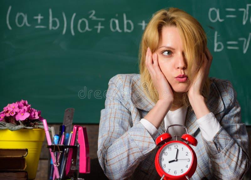 Se va el tiempo profesor con el despertador en la pizarra Tiempo De nuevo a escuela D?a de los profesores Estudio y educaci?n mod fotos de archivo