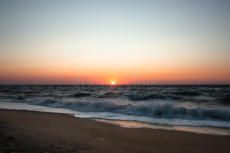 Sea beach at sunrise. Sea waves on a sandy beach. Tropical vacation background. Natural landscape. Sunset ocean horizo. N sky royalty free stock images