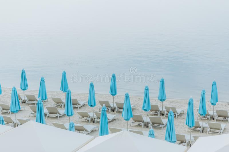 Sea ​​resort sand beach deck chairs blue umbrellas. Sea ​​resort white sand beach group deck royalty free stock images