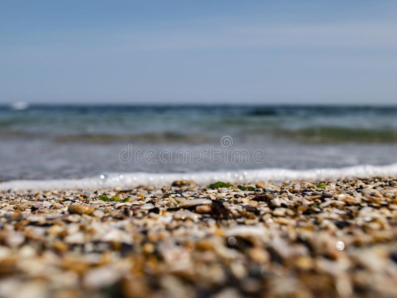 Sea small pebbles and shells on the seashore against the blue sky stock images