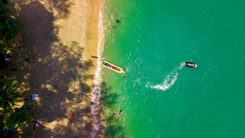 Sea attraction, happy people ride the inflatable watercraft boat from aerial view stock photos