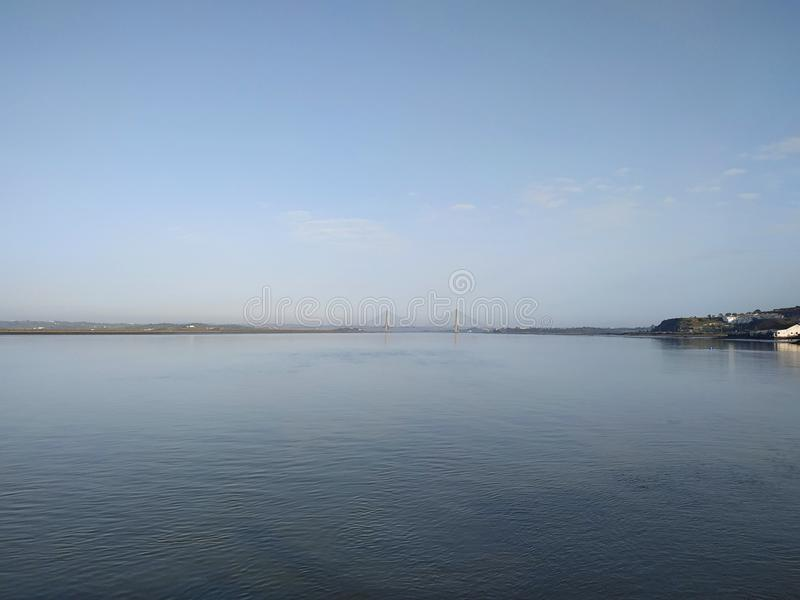 The sea in Ayamonte with The International Bridge, a suspension bridge between Spain and Portugal. In the back stock photos