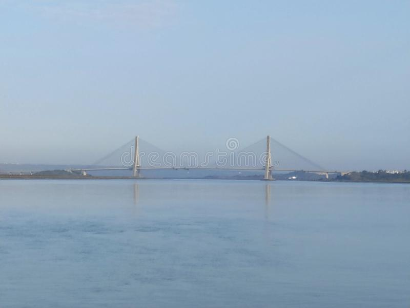The sea in Ayamonte with The International Bridge, a suspension bridge between Spain and Portugal. In the back royalty free stock photo