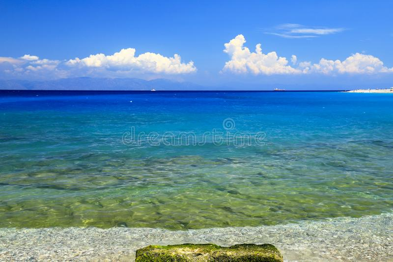 Sea background. Picturesque summer beach, pebbles in the surf line on a beautiful turquoise sea, Rhodes, Greee stock photography
