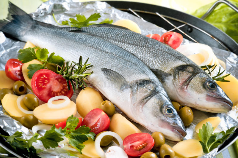 Sea-bass. With the vegetables on a grill royalty free stock photo