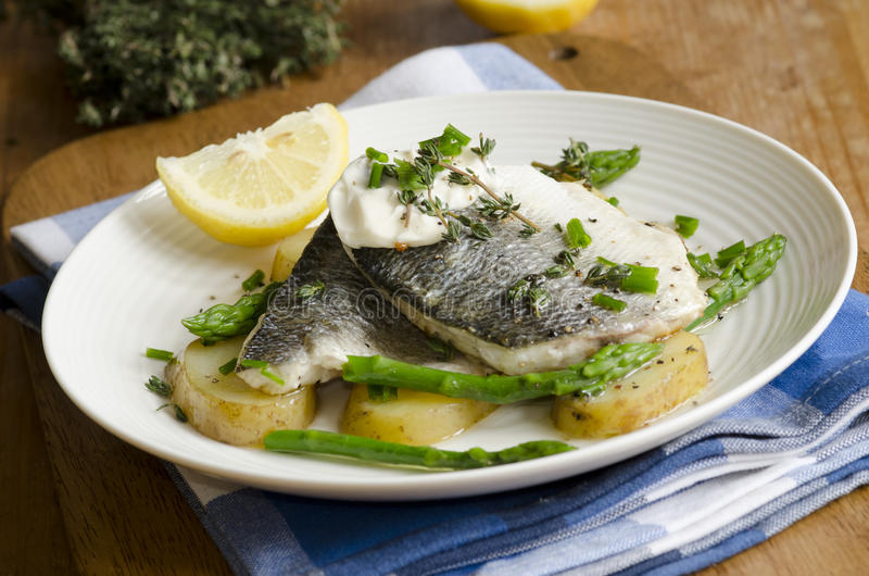 Sea bass. Grilled sea bass with asparagus and new potatoes royalty free stock photography