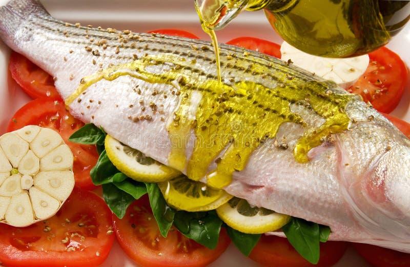 Sea bass. Preparing striped sea bass for cooking stock photos