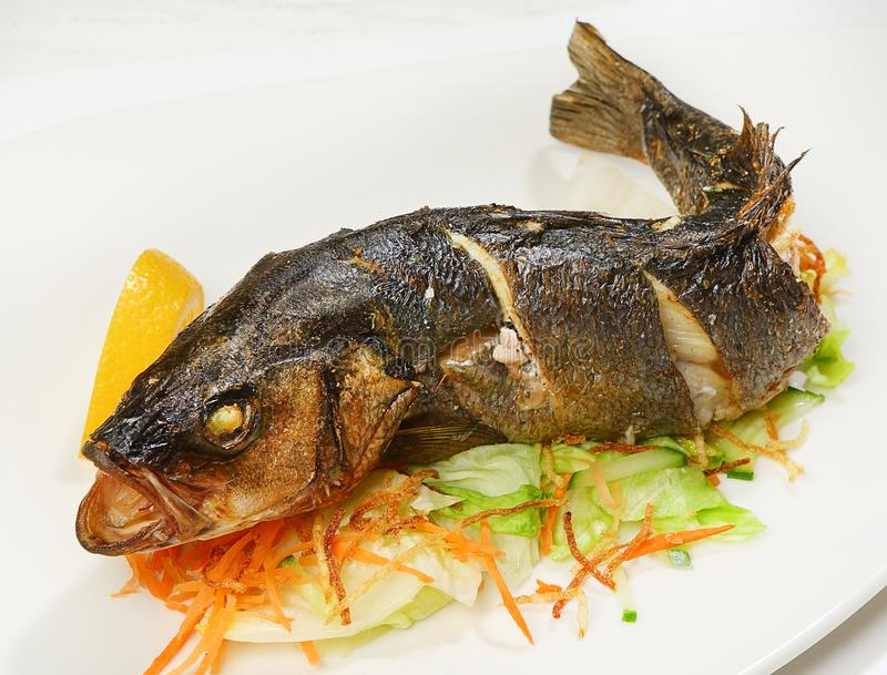 Sea bass baked with aromatic salt is served with a mix of salad leaves and carrots, potatoes and oyster sauce.  royalty free stock photo