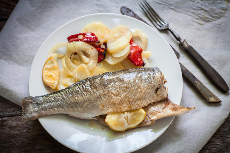 Sea bass baked. Sea bass fish baked with potato and red pepper royalty free stock image
