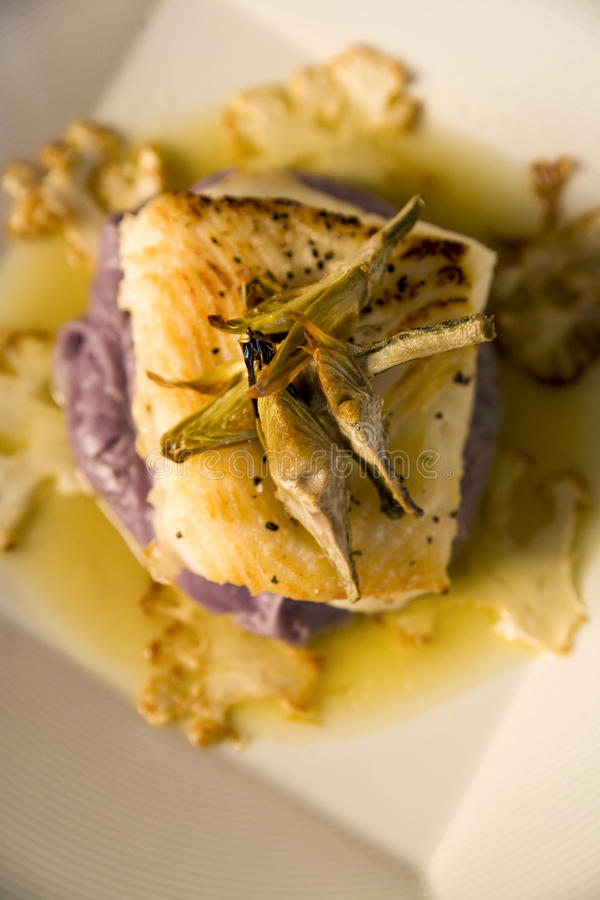 Sea bass on a bed of purple potato puree stock images