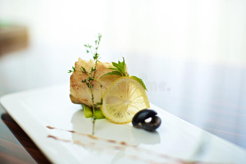 Sea bass canapé. With lemon on white plate stock photo
