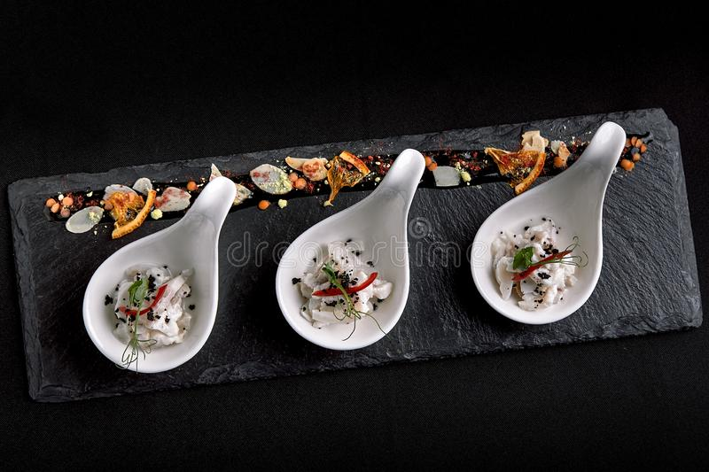 Sea bass ceviche mini portions served in beautiful Chinese spoons on a black plateau. Food concept for catering. stock images