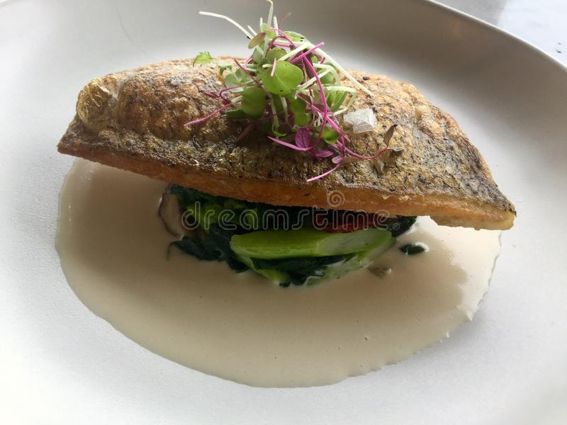 Sea bass classic. fish on spinach. Sea bass on Spinach with wine sauce stock photos