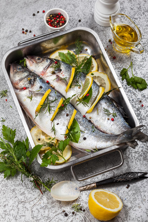 Sea bass before cooking. Sea bass with lemon, herbs and persian blue salt before cooking royalty free stock images