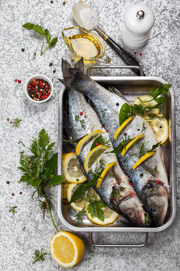 Sea bass before cooking. Sea bass with lemon,herbs and persian blue salt before cooking stock images