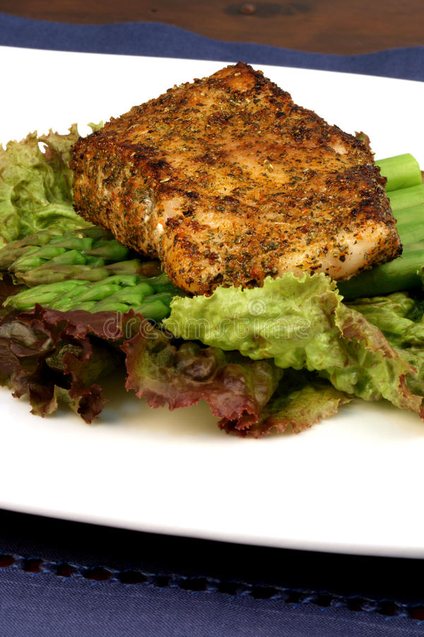 Sea bass dinner. Delicious grilled sea bass, seasoned with fine spices with asparagus and lettuce bed stock photo