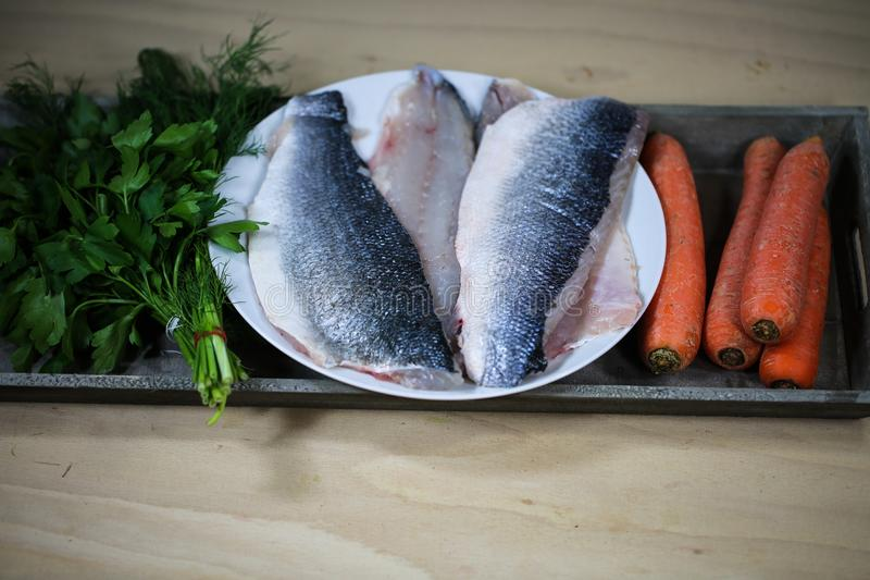 Sea bass filet with ingredients on wooden board. Loup de mer royalty free stock photography