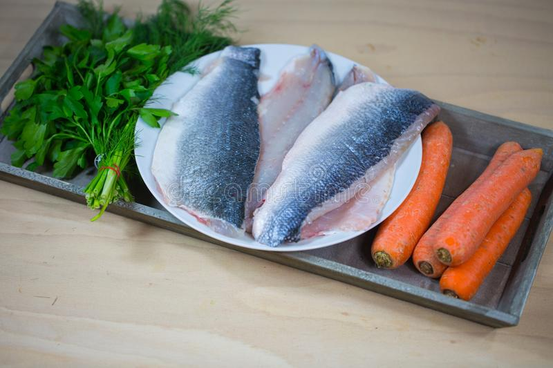 Sea bass filet with ingredients on wooden board. Loup de mer stock images