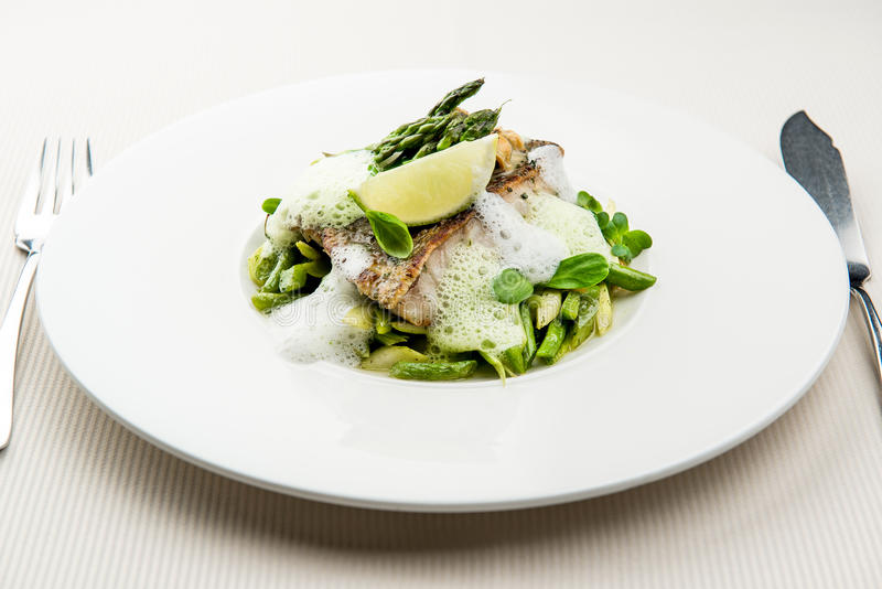 Sea bass fillet. With asparagus infused with sauce foam royalty free stock photos